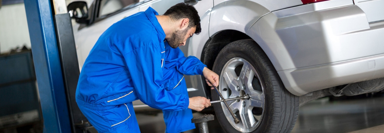 Auto Technician In Blue Jumpsuit Working On Car Tires